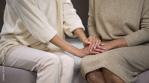 Fényképezés  Young lady holding and stroking hand of senior woman, calming and supporting