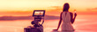 canvas print picture - Videography professional video camera shoot behind the scene shooting at hotel filming sunset scene banner panorama, luxury travel. Professional videography equipment shooting in summer destination.