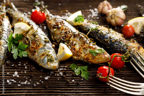 Foto op Aluminium Vis Fried fishes with addition of herbs, spices and lemon slices on a wooden background.