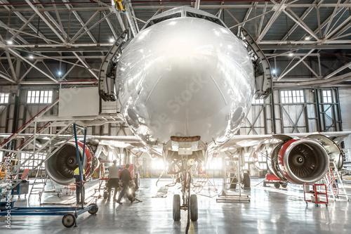 Passenger aircraft, nose close up. Maintenance of engine and fuselage repair in airport hangar
