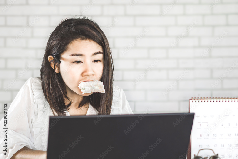 Fototapeta workaholic Asian woman busy with working and eating sandwich at her office desk