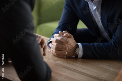 Purposeful confident restrained businessmen in suits sit at table opposite each other, close up male clenched hands in lock at desk Canvas Print