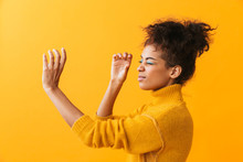 Portrait Of Beautiful African American Woman With Afro Hairstyle Looking Through Invisible Spyglass, Isolated Over Yellow Background