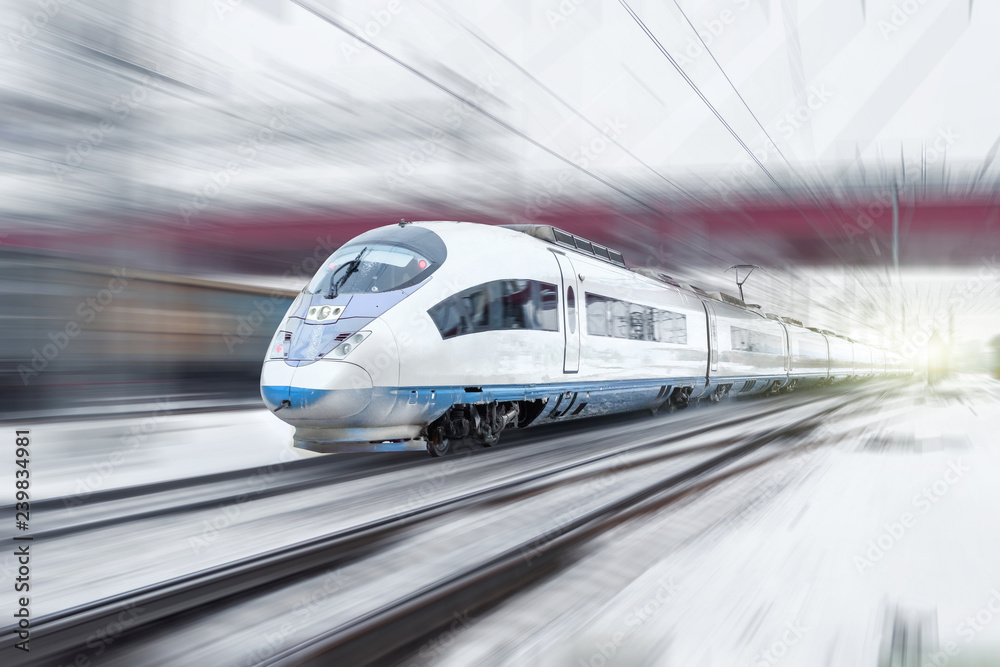 Fototapeta Train rides at high speed in winter around the snowy city industrial landscape