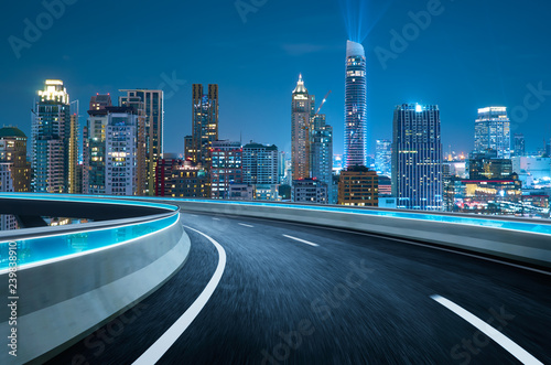 Fotobehang Nacht snelweg Curvy flyover highway moving forward road with Bangkok cityscape night scene view . motion blur effect apply
