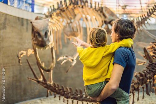 Photographie Dad and boy watching dinosaur skeleton in museum