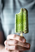 Midsection Of Man Holding Matcha And Mint Chocolate Chip Popsicle
