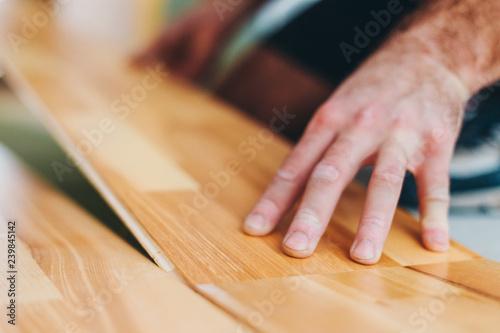 Obraz The master skillfully installs parquet - floating floor - floor work during finishing - fototapety do salonu