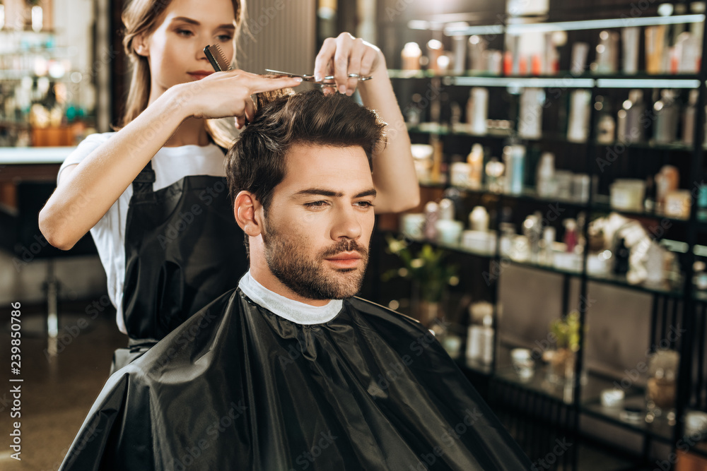 Fototapeta beautiful young hairdresser cutting hair to handsome man in beauty salon