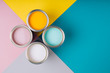 Leinwandbild Motiv Four open cans of paint on bright symmetry background. Yellow, white, pink, turquoise colors of paint. Place for text. Renovation concept.