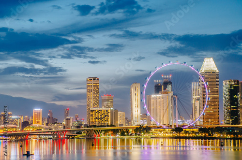View of the Giant Ferris wheel and Singapore city building background in sunset time ,Illuminated skyscrapers on a background on November 24, 2018