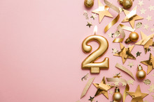 Number 2 Gold Celebration Candle On Star And Glitter Background
