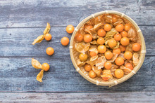 Cape Gooseberry Fruits In The Basket (Physalis Peruviana) On Wooden Background.Commonly Called Goldenberry, Golden Berry, Pichuberry.