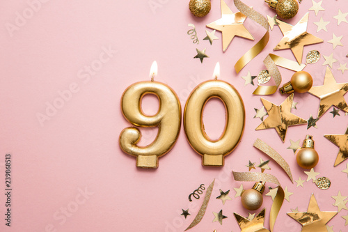 Valokuva  Number 90 gold celebration candle on star and glitter background