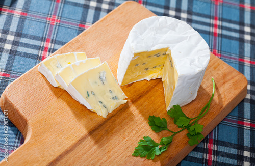 Soft blue cheese on wooden board with parsley