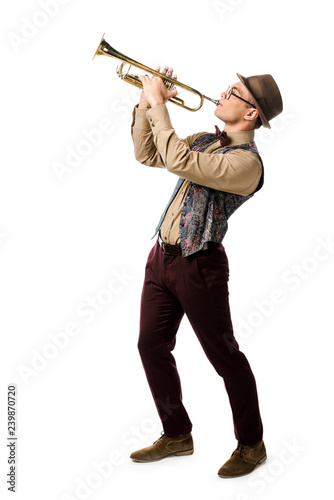Fotografia mixed race young man in hat and eyeglasses playing on trumpet isolated on white