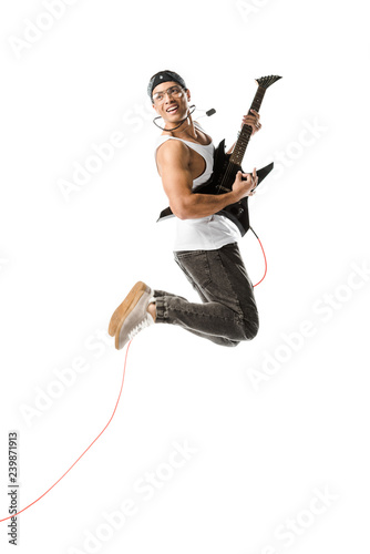 Obraz na plátně  cheerful young man jumping and playing on electric guitar isolated on white