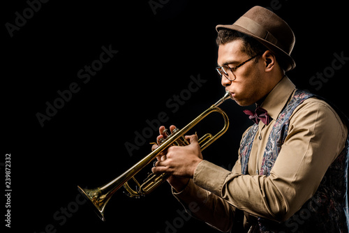 Photo Stands Music Band side view of mixed race male jazzman in hat and eyeglasses playing on trumpet isolated on black