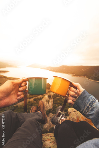 Poster Camping Pov image of couple holding enamel cups on mountain peak