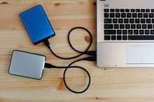 Many Colorful Portable External Hard Drives USB3.0 Connect To Laptop Computer On Wooden Background