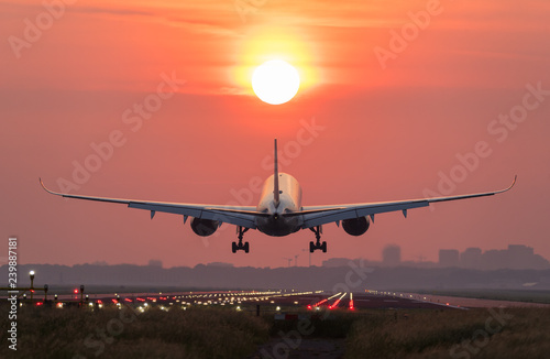 Tuinposter Airplane is flying to the sun during a beautiful early morning sunrise.