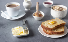 Butter And Bread For Breakfast With Cup Of Coffee, Granola, Honey And Jam Over Grey Stone Background.