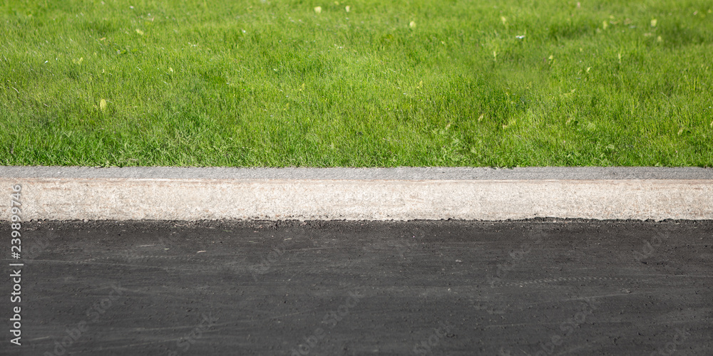 Fototapeta Green Grass Grows Near Black Asphalt, Separated By Concrete Border. Road And Lawn Divided By Concrete Curb.