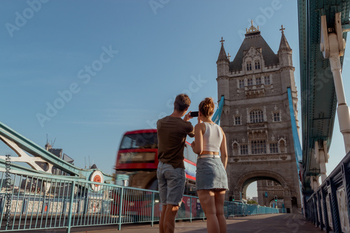 couple is taking a picture of a red double decker bus on the tower bridge in Lon Wallpaper Mural