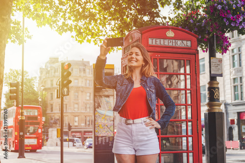 Fototapeta  happy young girl taking a selfie in front of a phone box and a red bus in London