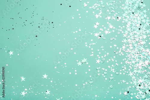 Silver and pink star glitter on teal pastel background. Festive concept. Place for design.