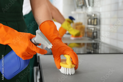 Female janitor cleaning kitchen counter with brush, closeup