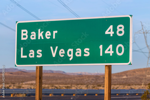 Late afternoon view of Las Vegas 140 miles highway sign on I-15 near Barstow in California.