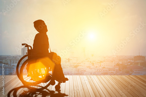 Valokuva  Silhouette of disabled person or wheelchair have sunset background