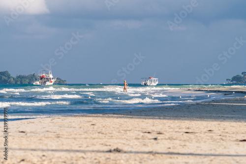Fotografie, Obraz  Caucasian woman, mid 40s, wearing two piece swimsuit walking into the ocean on S