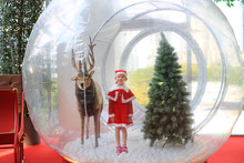 Adorable Little Child Girl In Santa Costume Dress Playing In Big Winter Snow Globe With Reindeer On Christmas Time. Merry Xmas And Happy New Year.