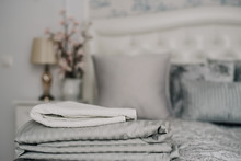 Stacks Grey White Bed Linen And Towels Textiles Clothing On Bed. Comfort, Design, Cozy Bedroom