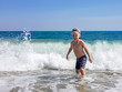 A little blond boy is playing on the seashore, laughing, running away from the waves against the background of huge waves and splashes, Calabria, Italy