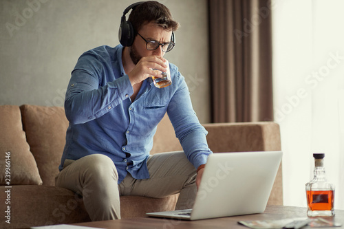 Photo businessman is drinking whisky while working at business project from a home