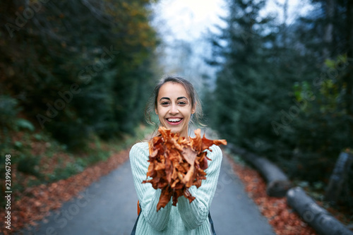 Fotografie, Obraz  Portrait of a happy woman playing with autumn leaves on the road in forest