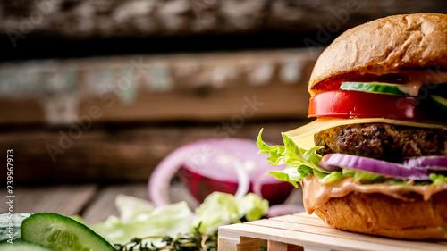 Cuadros en Lienzo fragment of homemade tasty hamburger on wooden vintage table