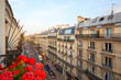 Paris, ancient buildings facades and street in a warm summer sunset in France