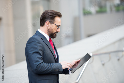 Fotografie, Obraz  Profile of concentrated mature manager using a tablet in the street