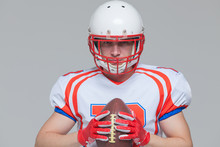 American Football Sportsman Player Wearing Helmet Holding Rugby Ball Isolated On Grey Background