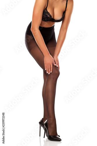 Fotografía  A woman adjust her black high waist nylon stockings on white background