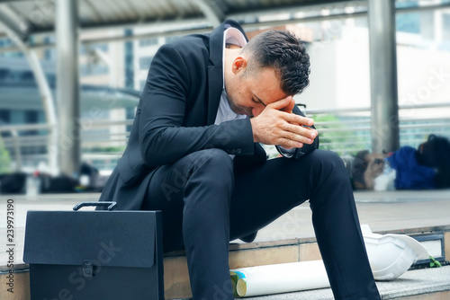 Fotografija  Businessman sit on the stairs and feel stressed