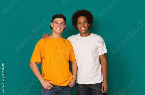 Fotografie, Obraz  Two best friends hugging and looking at camera over background