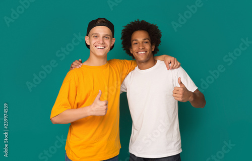 Fotografiet  Diverse teens showing thumbs up over blue background
