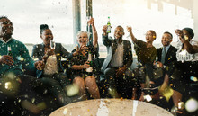 Group Of People Celebrating And Toasting With Confetti Falling