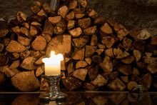 Candle With Logs On A Background And Reflection On A Floor. Copy Space.