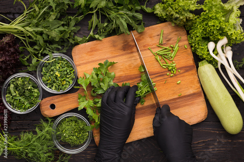 Fotografia, Obraz  Hands in black disposable gloves cutting parsley